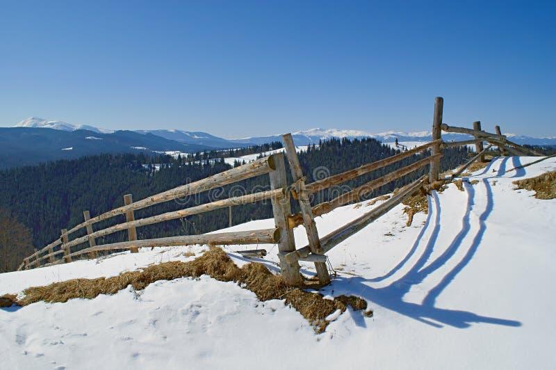 Landschaft mit altem Bretterzaun am schneebedeckten Hügel stockfotografie