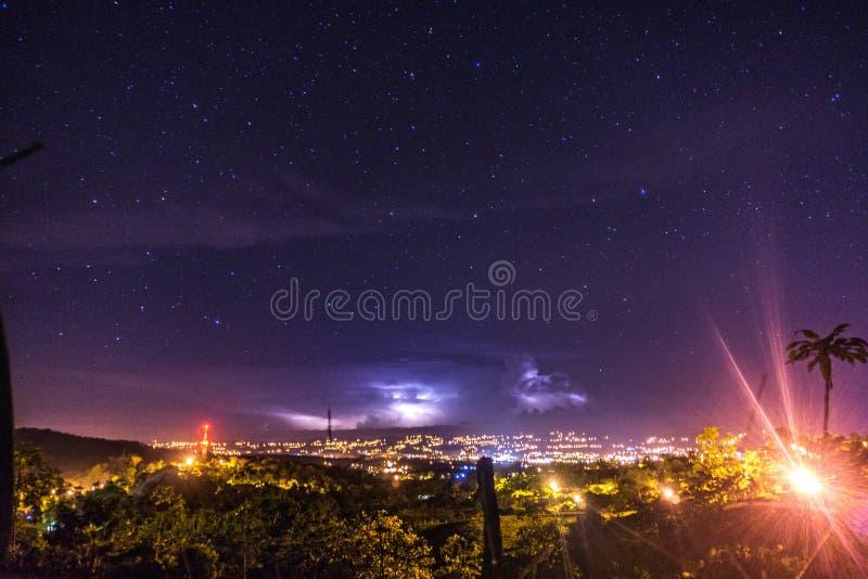 Landschaft mit Ansicht zu den ligths Stadt des elektrischen Sturms im sternenklaren nigth lizenzfreie stockfotos