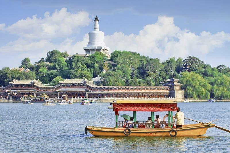 Landschaft mit Ausflugboot auf Beijing Beihal See mit stupa auf Hintergrund lizenzfreie stockfotografie