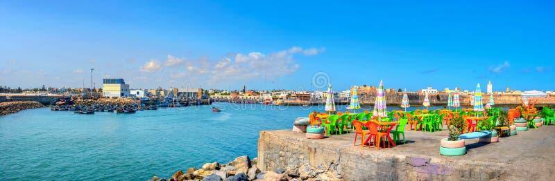 Landschaft mit bunten Straßencafés am Kai des Fischereihafens von Essaouira Marokko, Nordafrika stockfoto