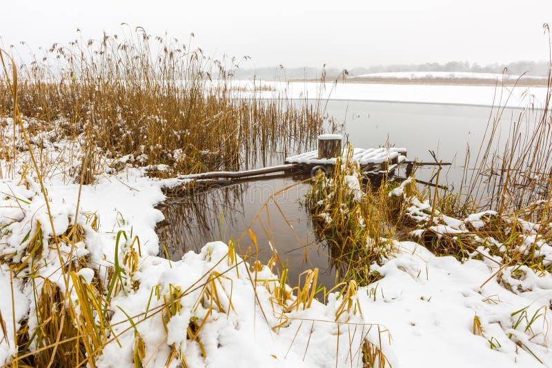 Landschaft mit der Anlegestelle bedeckt durch Schnee lizenzfreies stockbild