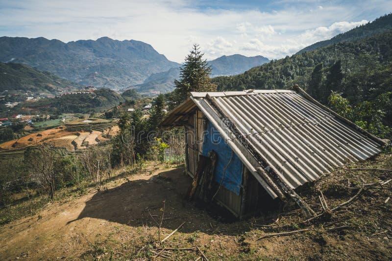 Landschaft mit einer Hütte in den Terrassen des ungeschälten Reises Schlechte alte Wohnung in den Bergen auf dem Hintergrund von  lizenzfreie stockfotos