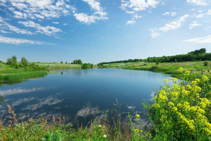 Landschaft mit Teich und Hügeln lizenzfreie stockfotografie