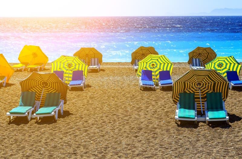 Landschaft von Elle-Strand auf Rhodos-Insel Panorama mit Sandseeküste mit Wagenaufenthaltsräumen unter Regenschirmen und klarem b stockfotos
