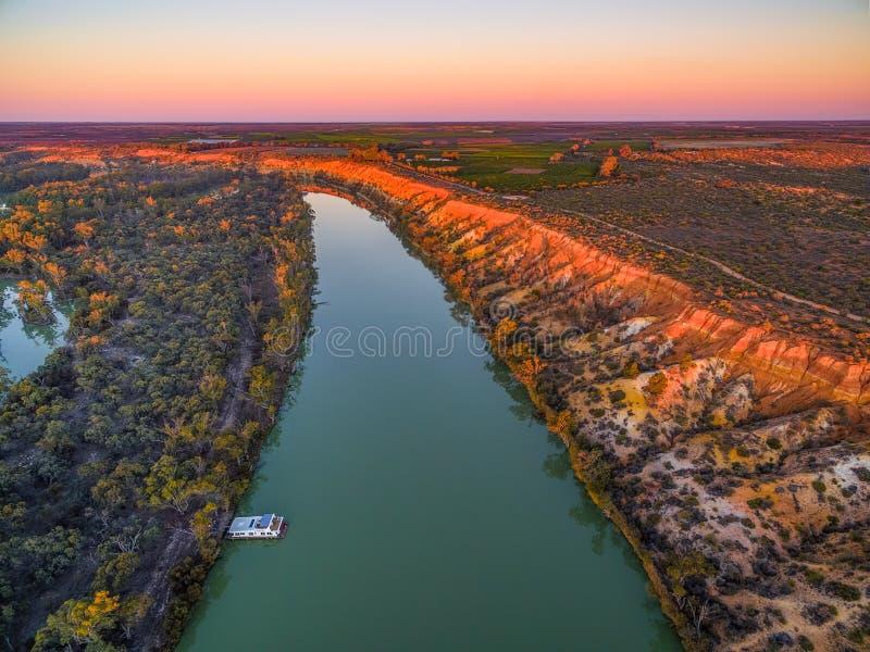 Landschaft von Sandsteinklippen über Murray River und festgemachtem Hausboot bei Sonnenuntergang stockfoto