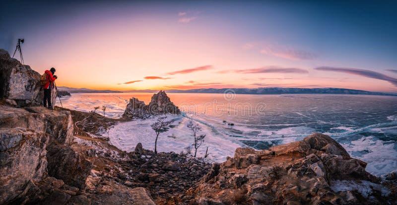 Landschaft von Shamanka-Felsen bei Sonnenuntergang mit natürlichem brechendem Eis in gefrorenem Wasser auf dem Baikalsee, Sibirie lizenzfreies stockfoto