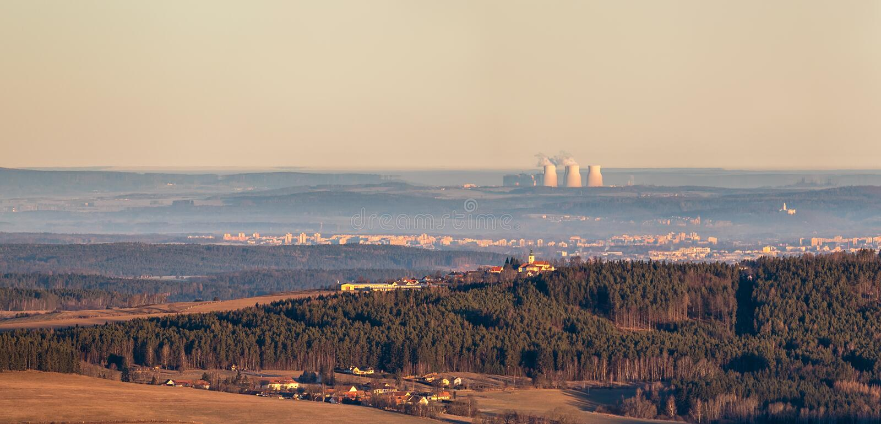 Landschaft - Wald und Hügel mit Kirche im Vordergrund und Kernkraftwerk am Horizont lizenzfreie stockfotografie