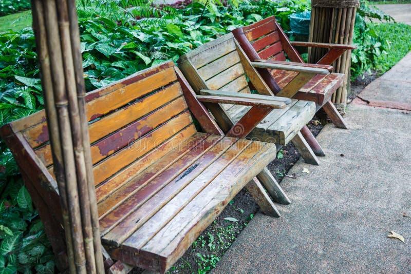 Landschaftlich gestaltete Designarchitekturholzbank und -stühle für liegen Ihr hinterer naher Ziergarten des grünen Grases parken stockbild