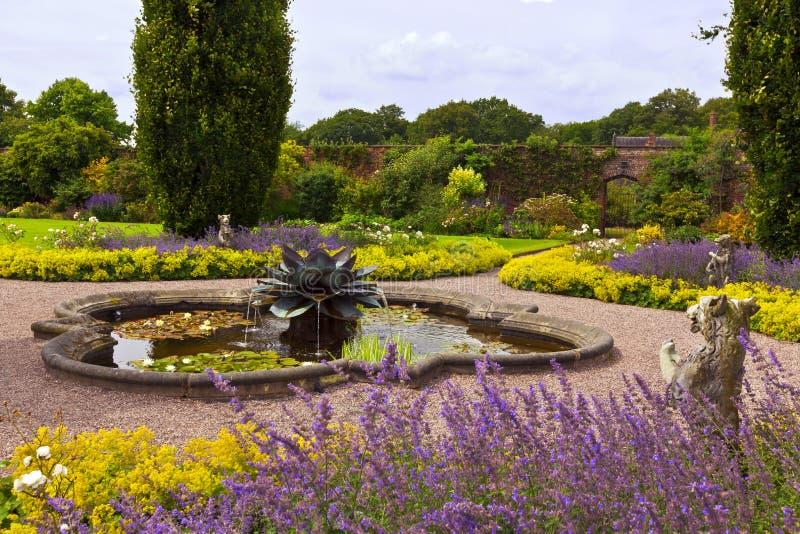 Landschaftlich gestalteter Garten mit Brunnen stockbilder