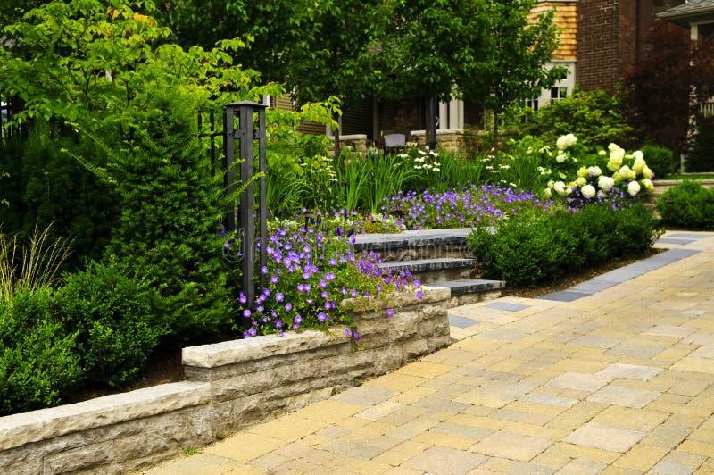 Landschaftlich verschönerter Garten und Stein gepflasterte Fahrstraße stockfotos