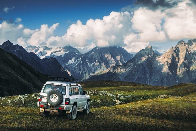 Landschaftsansicht des Gebirgszugs und Autos des nicht für den Straßenverkehr in der Wiese, Nationalpark Svaneti, Georgia stockbilder