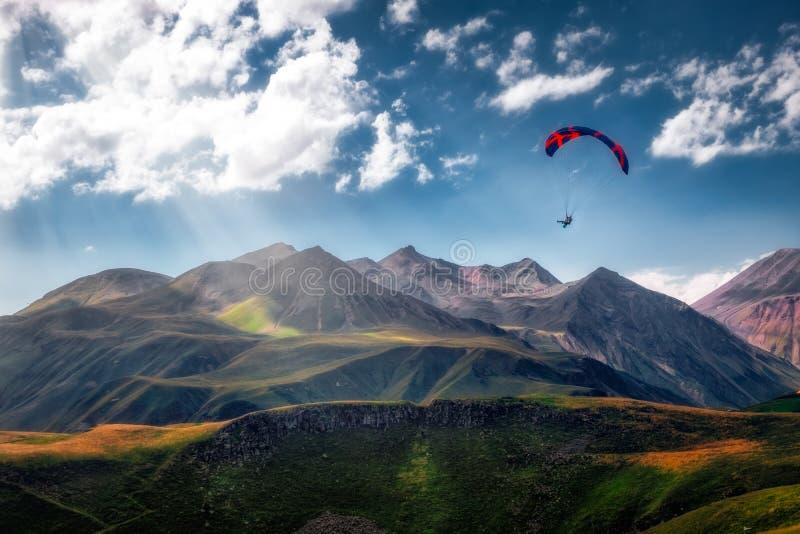 Landschaftsansicht des Gleitschirmfliegens über schönen Bergen und Himmel lizenzfreie stockfotografie