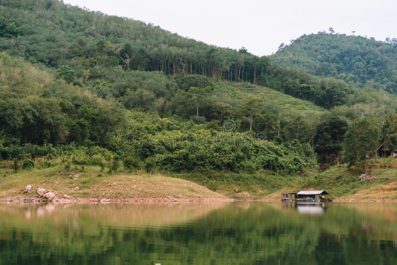 Landschaftsansicht des Knalles Lang Reservoir mit Hausfloss in der Lagune lizenzfreie stockbilder