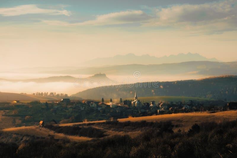 Landschaftsansicht des traditionellen Dorf- und Spissky-hradschlosses mit hohen Tatras-Bergen, Slowakei lizenzfreies stockbild
