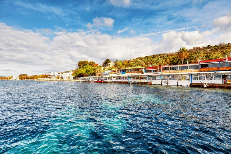 Landschaftsansicht von Fischrestaurants an der Küste an einem sonnigen Wintertag in Gumusluk, Bodrum, Mugla, die Türkei lizenzfreies stockfoto