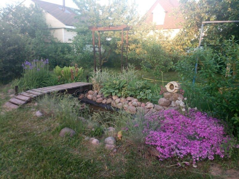 Landschaftsentwurf: Holzbrücke, Bogen, Teich, Krug und purpurrote Blumen am Dorf stockfotografie