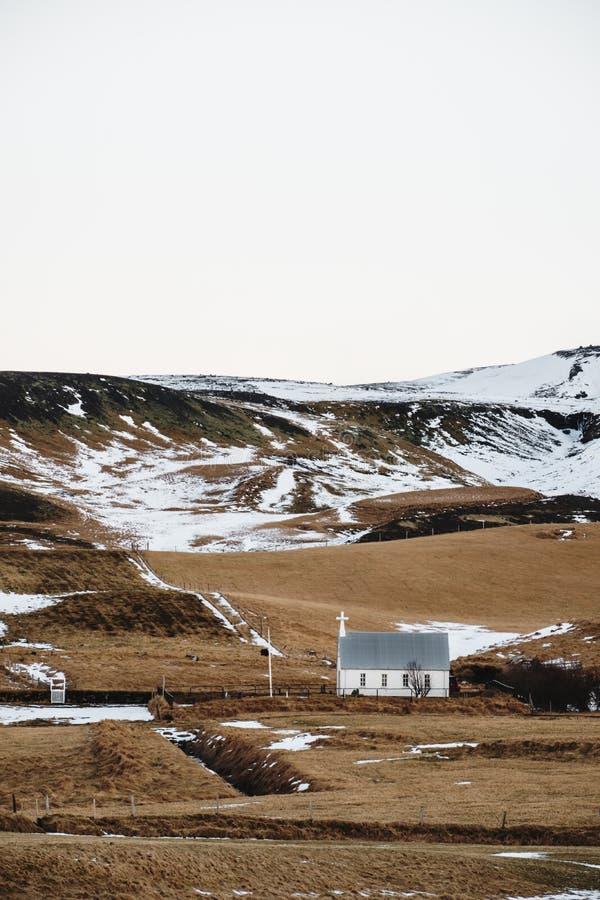 Landschaftslandschaft, mit kleinem Kirchenstand allein auf Hügeln in Island lizenzfreies stockbild