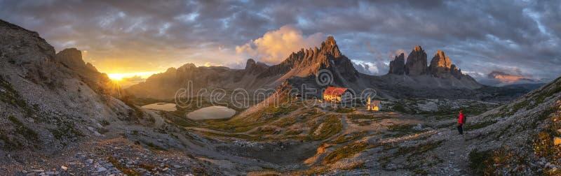 Landschaftspanoramaansicht des Hauses und des Berges mit Goldhimmel auf Sonnenuntergang von Tre Cime, Dolomit, Italien stockfoto
