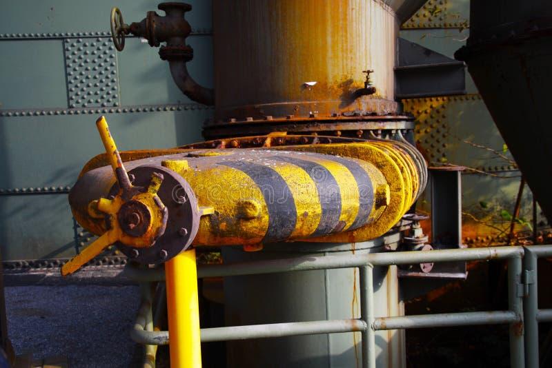 Landschaftspark杜伊斯堡,德国:关闭控制阀被隔绝的黑和黄色镶边生锈的老轮子  库存图片