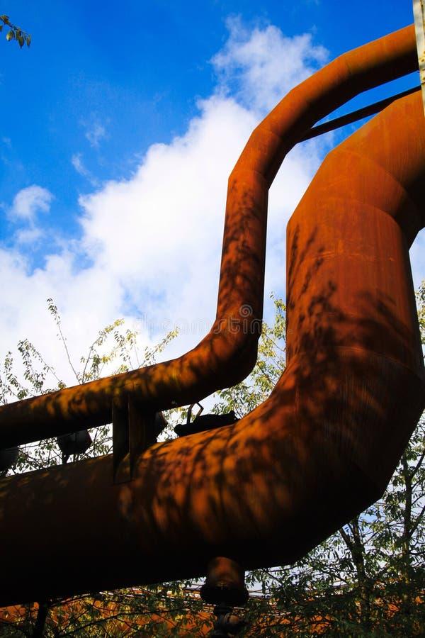 Landschaftspark Дуйсбург, Германия: Взгляд низкого угла на изолированном изогнутом вытравленном трубопроводе против голубого неба стоковая фотография