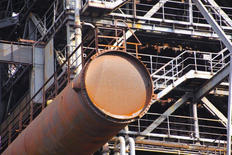 Landschaftspark Дуйсбург, Германия: Вытравленная ржавая трубка выступает от стальной башни с лестницами стоковые фотографии rf