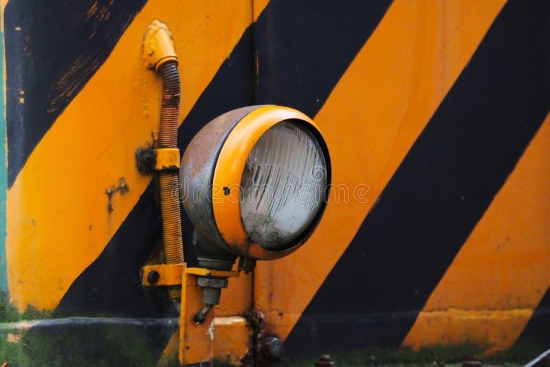 Landschaftspark Duisburg, Alemanha: Feche acima da lâmpada elétrica de uma locomotiva velha com as listras amarelas e pretas foto de stock