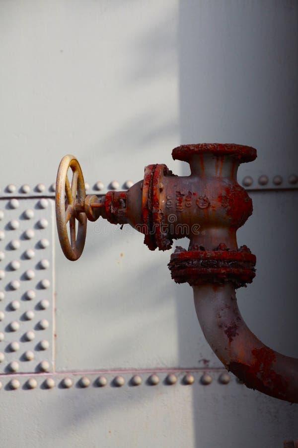 Landschaftspark Duisburg, Alemanha: Feche acima da válvula de controle oxidada vermelha isolada do relevo com os flocos do descas imagens de stock royalty free