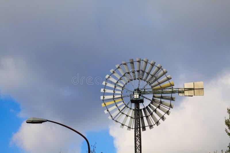 Landschaftspark Duisburg, Duitsland: Sluit omhoog van geïsoleerd windwiel tegen blauwe hemel en wolken stock foto