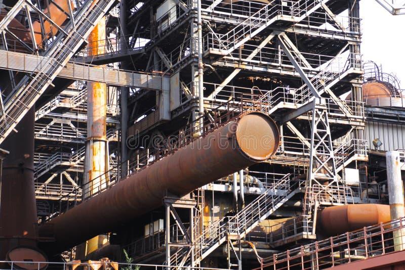 Landschaftspark Duisburg, Niemcy: Korodująca ośniedziała tubka sterczy od stali wierza z schodami obraz stock