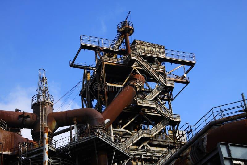 Landschaftspark Duisburg, Tyskland: Sikt för låg vinkel på trappor in i djupblå himmel på det anfrätta tornet med den rostiga rör arkivbilder