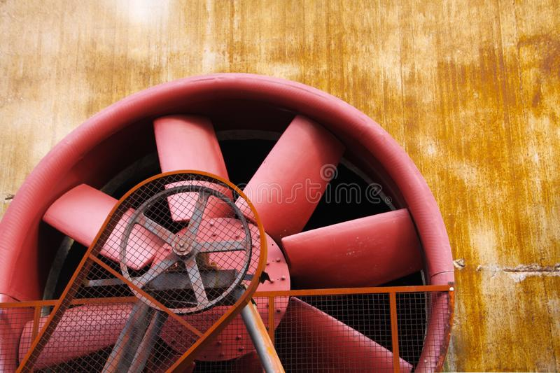 Landschaftspark Duisburg, Tyskland: Stäng sig upp av den röda turbinen med körningsbältet och den rostiga stålväggen royaltyfri bild