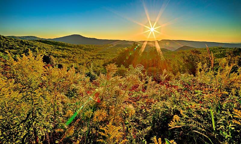 Landschaftssonnenaufgang am braunen Berg übersehen stockbild