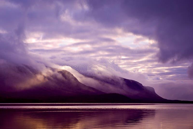 Landschap. Bergen en meer in mist in ochtend met purper col. royalty-vrije stock foto