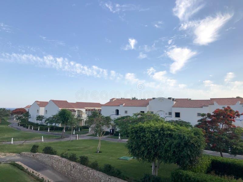 Landschap met de hoogten Arabische Moslim witte steengebouwen, plattelandshuisjes, huizen met rode tegelkreken en tropische groen stock foto