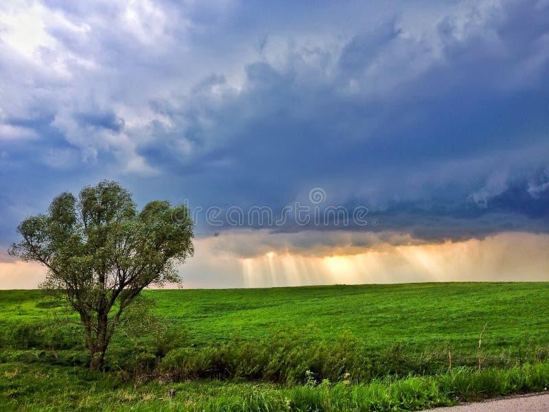 Landschap met donkere wolk en stralen van de zon stock foto