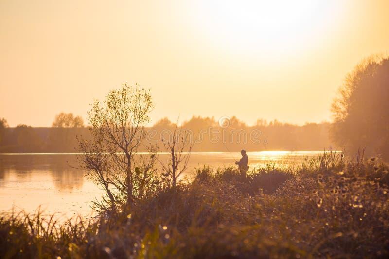 Landschap met een rivier, bomen en een visser op de rivierbank tijdens de zonsondergang in de warme herfst colors_ stock fotografie