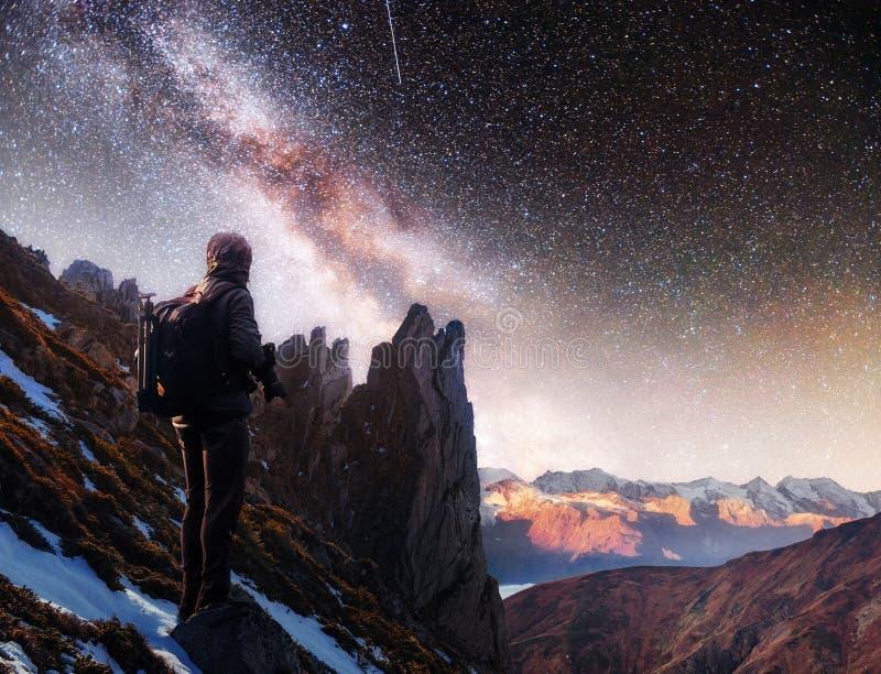 Landschap met melkachtige manier, de sterren van de Nachthemel en silhouet van een bevindende fotograafmens op de berg royalty-vrije stock afbeeldingen