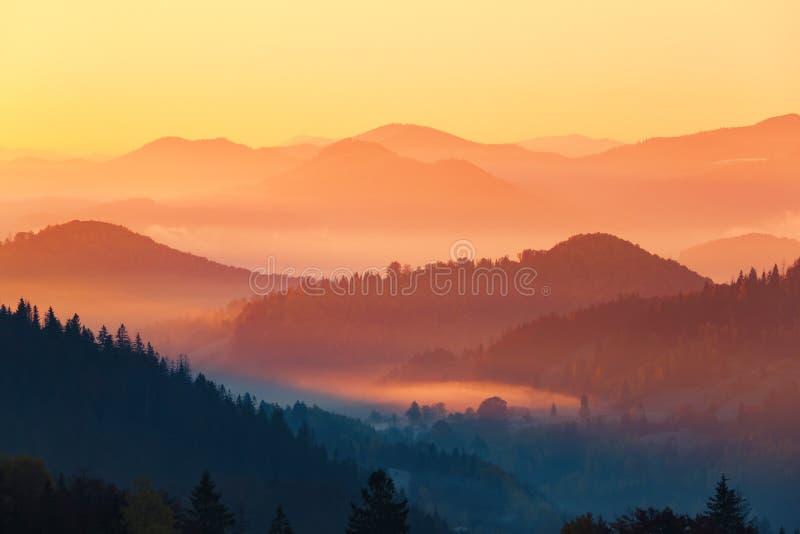 Landschap met mooie die bergen, gebieden en bossen met dikke ochtendmist worden behandeld De interessante zonsopgang informeert o royalty-vrije stock foto's