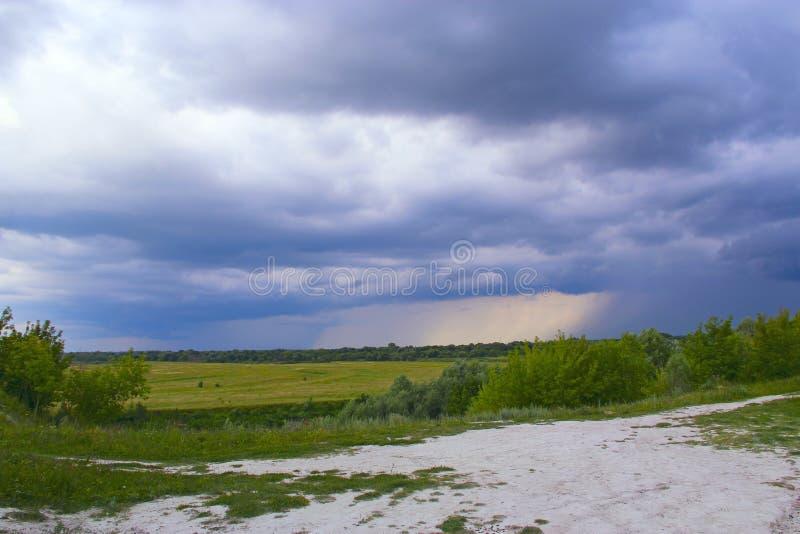 Landschap met onweerswolk over gebied en bosstromen van regen in afstand stock afbeeldingen