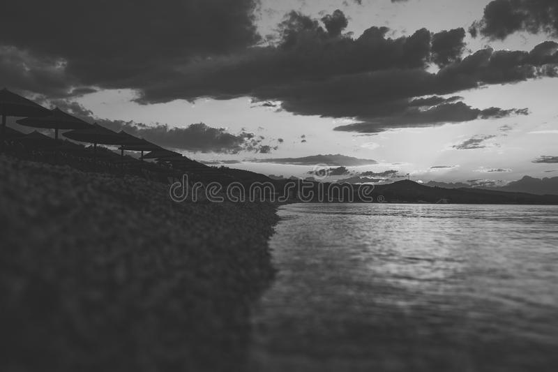 Landschap met strand, zeewater, paraplu's en lanterfanters in avond Horizon na zonsondergang met laatste stralen van zon en stock afbeelding