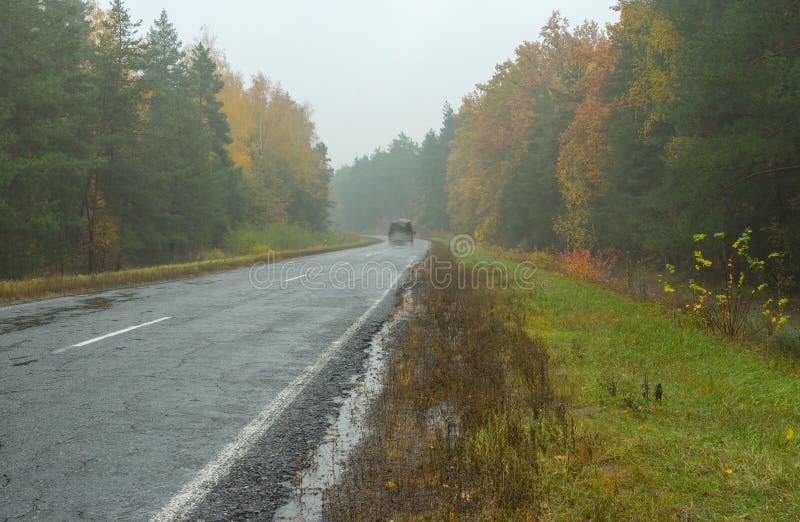 Landschap met weg, regenachtig weer en eenzaam motorvervoer royalty-vrije stock afbeelding