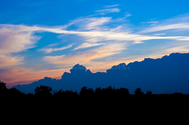 Landschap met wolken en silhouetten van bomen royalty-vrije stock foto