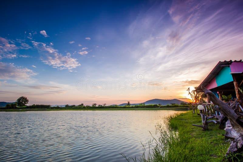 Landschap met zonsondergang over meer stock fotografie