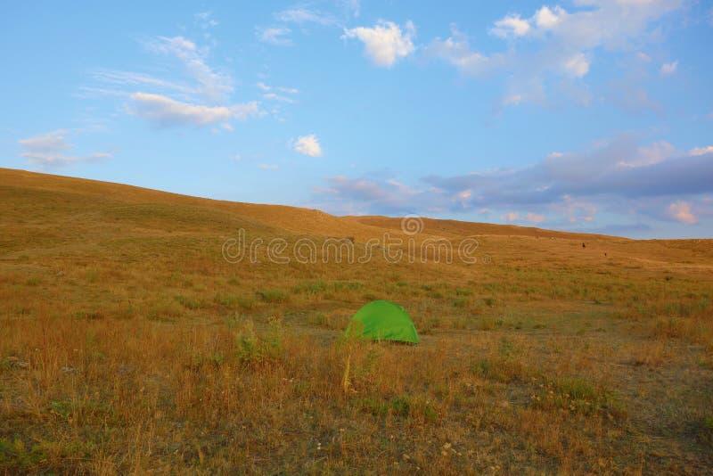 Landschap tijdens zonsondergang in Geghama-bergen met een groene tent in Armenië stock fotografie