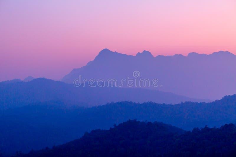 Landschap van berglaag in van de ochtendzonsopgang en winter mist stock afbeeldingen