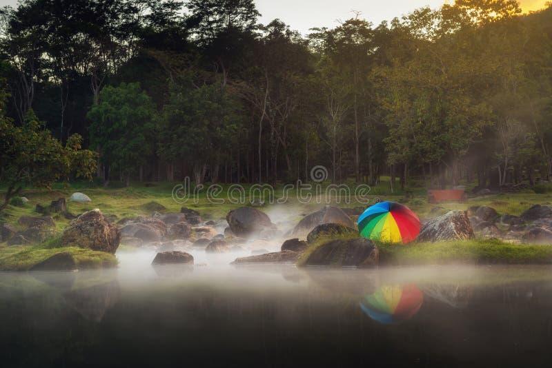 Landschap van de hete lentes met kleurrijke paraplu op zonsondergangscène , Natuurlijke stoom van geothermisch in nationaal park  stock afbeelding