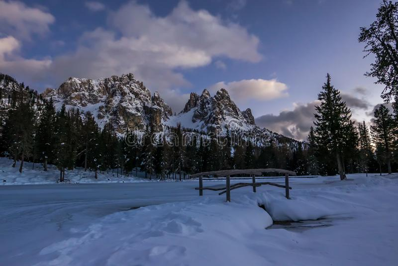 Landschap van de nacht het alpiene winter met kleine brug op bevroren meer stock afbeelding