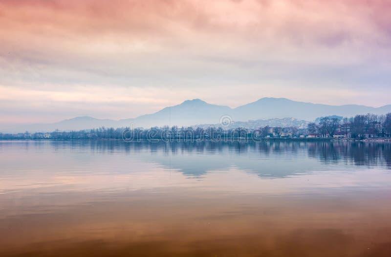 Landschap van de stad van Ioannina omhoog door rood, oranje kleurenzonlicht wordt aangestoken a die stock afbeeldingen