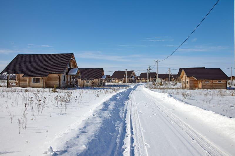 Landschap van dorp met houten plattelandshuisjes in zonnige de winterdag stock foto