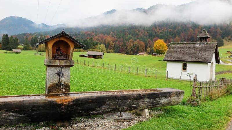 Landschap van een Beierse landbouwgrond met een houten trog, buitenhuizen & schuren in een boerderij op een mistige de herfstocht stock afbeeldingen